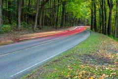 Een onduidelijk beeld van koplampen en brakelights op een rijweg stock afbeelding
