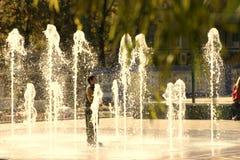 Een ongebruikelijke jongen bevindt zich in het centrum van de fontein royalty-vrije stock fotografie