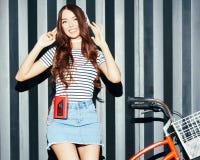 Een ongelooflijk mooi Aziatisch meisje in een de zomeruitrusting geniet van de muziek Hoofdtelefoons en rode uitstekende cassette Stock Afbeelding