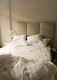 Een onopgemaakt bed in een hotelruimte Stock Foto's