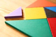 Een ontbrekend stuk in een vierkant tangram raadsel, over houten lijst royalty-vrije stock afbeelding