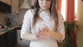 Een ontevreden meisje breekt het ruwe deeg in de keuken, zet het in een bal en werpt het op de lijst stock footage