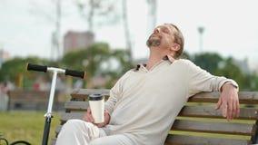 Een ontspannen, aantrekkelijke mens op middelbare leeftijd met lang grijs haar drinkt koffie van een beschikbaar glas op een bank stock videobeelden