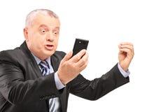 Een ontstemde manager die in kostuum op een mobiele telefoon gillen stock afbeelding