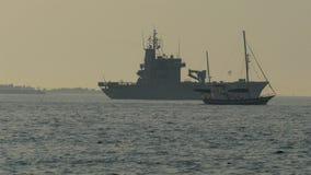 Een oorlogsschip op standy en een kleine boot die van Viking GH4 4K UHD kruisen stock videobeelden