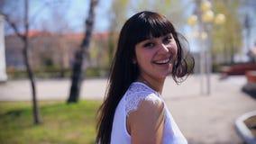 Een oosters mooi meisje in een witte blousegangen door het park, draait, onderzoekt de camera en glimlacht stock videobeelden