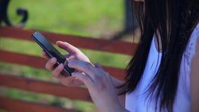 Een oosters mooi meisje in een witte blousezitting in een park op een bank houdt een smartphone met het gebroken scherm stock videobeelden