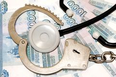 Een open armband van politiehandcuffs en een medische phonendoscope liggen op de achtergrond van Russisch geld Schending van de w stock afbeeldingen