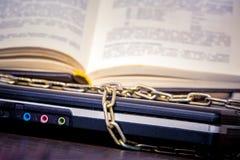 Een open boek ligt op laptop die door een ketting wordt verbonden Boeken in plaats van computers Liefde aan read_ royalty-vrije stock foto's