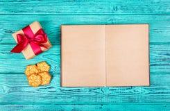 Een open boek met blanco pagina's, een giftvakje met een boog en Kerstmiskoekjes Koekjes in de vorm van sneeuwvlokken en een Kers Royalty-vrije Stock Afbeelding