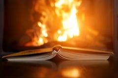 Een open boek naast de open haard stock afbeelding