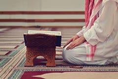Een open Heilige quran met houten tribune met het bidden van mensen op achtergrond royalty-vrije stock foto