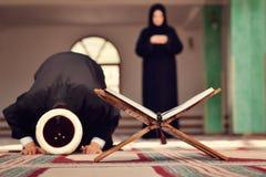 Een open Heilige quran met houten tribune met het bidden van mensen op achtergrond stock afbeeldingen