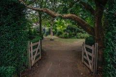 Een open houten poort op het landbouwbedrijf die in een helder comfortabel bos leiden stock afbeelding