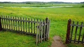 Een open poort in een houten omheining en een groene weide voorbij het, de weg in het kader De bewolkte zomer of de recente lente stock afbeelding