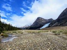 Een open vallei van rotsen en kreken die naar de wintertalingswateren leiden van Berg Lake stock fotografie
