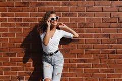 Een openluchtportret van een jong mooi hipstermeisje met lang donkerbruin krullend meisjeshaar royalty-vrije stock afbeelding