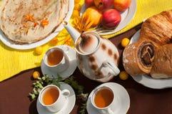 Een openluchtsamenstelling met theekoppen, een theepot, een plaat van pannekoeken, gebakje, rijp fruit en gebied bloeit op een he Stock Fotografie