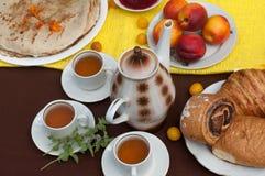Een openluchtsamenstelling met theekoppen, een theepot, een plaat van pannekoeken, gebakje, rijp fruit en gebied bloeit op een he Royalty-vrije Stock Afbeeldingen