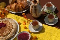 Een openluchtsamenstelling met theekoppen, een theepot, een plaat van pannekoeken, gebakje, rijp fruit en gebied bloeit op een he Stock Foto's