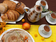 Een openluchtsamenstelling met theekoppen, een theepot, een plaat van pannekoeken, gebakje, rijp fruit en gebied bloeit op een he Royalty-vrije Stock Fotografie