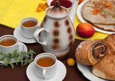 Een openluchtsamenstelling met theekoppen, een theepot, een plaat van pannekoeken, gebakje, rijp fruit en gebied bloeit op een he Stock Afbeeldingen