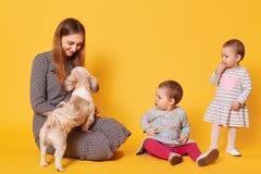 Een opgetogen gelukkige mammaspelen met haar favoriet huisdier, zittend op de vloer, die het bekijkt De verraste tweelingdochters stock fotografie