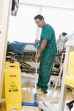 Een oppasser die de Vloer in een Afdeling van het Ziekenhuis dweilt Stock Foto