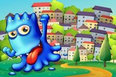 Een opschepperig blauw monster boven de heuvel over de gebouwen Stock Foto's