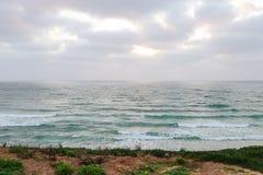 Een opschrikkend landschap van een kalme overzees, een blauwe hemel en een groen gras stock foto