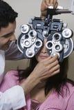 Een optometrist Adjusting Panels Of Phoropter terwijl het Onderzoeken van Patiënt Stock Foto's