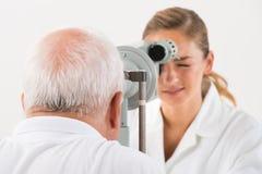 Een Optometrist Doing Sight Testing voor Patiënt stock afbeeldingen