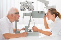 Een Optometrist Doing Vision Testing voor Mannelijke Patiënt royalty-vrije stock foto