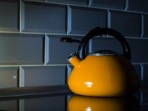 Een oranje ketel bevindt zich op een inductiehaardplaat royalty-vrije stock fotografie