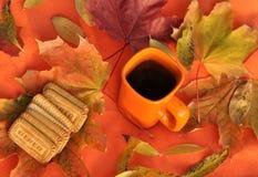 Een oranje kop thee, kleurrijke esdoornbladeren en koekjes op een oranje oppervlakte Royalty-vrije Stock Fotografie