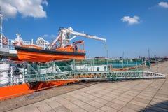 Een oranje motorsloep hangt aan de kant van het schip en de doorgang is op de kade royalty-vrije stock afbeeldingen