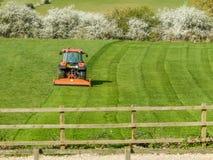 Een oranje tractor scherp gras op landbouwgrond royalty-vrije stock foto