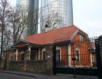 Een oud blokhuis in de stad Wolkenkrabber op de achtergrond Royalty-vrije Stock Foto's