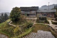 Een oud blokhuis en terrasvormige padiegebieden hoog in de bergen van Guizhou-provincie in China stock foto's