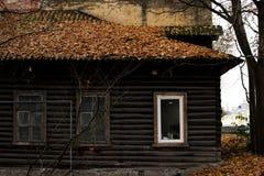 Een oud blokhuis, het dak waarvan met de herfst behandeld is gaat weg Een combinatie van antiquiteit en een nieuw wit plastic ven royalty-vrije stock fotografie