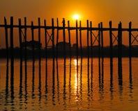 Een oud cijfer die de brug u-Bein kruisen bij zonsondergang, Amarapura, Myanmar (Birma). Royalty-vrije Stock Afbeeldingen