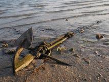 Een oud die anker op het strand wordt gelaten vallen stock afbeelding