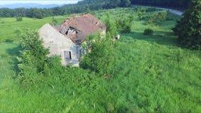 Een oud en verlaten huis in een berg met een geruïneerd dak stock footage