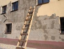 Een oud gebouw met beschadigde voorgevel met houten ladder door de muur stock afbeeldingen