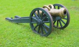 Een oud kanon tegen een groen gras Stock Foto