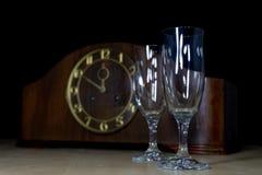Een oud klok en een glazenhoogtepunt van champagne op Nieuwe Year' s Vooravond FI stock foto's