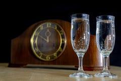 Een oud klok en een glazenhoogtepunt van champagne op Nieuwe Year' s Vooravond FI stock foto