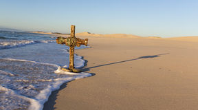 Een oud kruis op zandduin naast de oceaan met een kalme zonsopgang Stock Afbeeldingen