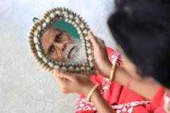Een oud mensens gezicht denkt van de spiegel na maar een meisje houdt die spiegel Stock Foto's