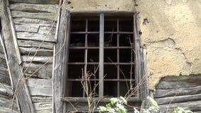 Een oud venster met bars op het verlaten huis stock video